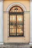 Barred old window between two white columns. A window with an arch and a lattice with peaks on a yellow wall between two white columns. Old European architecture royalty free stock photography