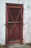 Barred Red Door. A Barred Red Door Rusting While Out of Use stock image