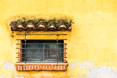 Barred & shuttered window in yellow wall, Central America stock photos