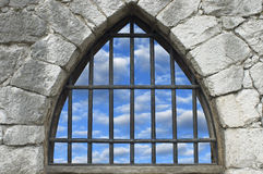 Barred window. In stone wall of castle Stock Photography