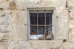 Barred window detail. Old house facade including a barred window and a pair of shoes Stock Photography