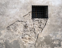 Barred window in eroded wall Royalty Free Stock Photo