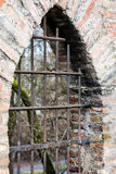 Barred window in a historic city wall Stock Images