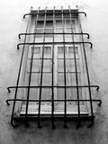 Barred window. A monochrome barred window on the external wall of a house in a Ligurian village in Liguria, Italy Stock Image