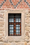 Barred window in a red brick wall. On ancient facade Royalty Free Stock Image