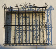 Barred window with shadows. Wrought Iron Grill or bars on Window in Alora, Andalucia casting shadows on wall Royalty Free Stock Photography