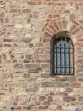 Barred window in stone wall. A view of a window with heavy iron security bars in an old stone and brick wall Royalty Free Stock Image