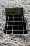 Barred window in the stone wall Royalty Free Stock Photo