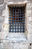 Barred window in the stone wall of the castle Santa Barbara, Alicante, Spain Stock Photos