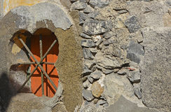 Barred window in wall, Funchal, Madeira, Portugal. Barred and shuttered window opening in rustic stone wall. Funchal, Madeira, Portugal Royalty Free Stock Images