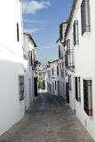 Barred windows. Cobbled street pavement, with white houses on the sides to see the solid background of Grazalema in the Spanish province of Cadiz Stock Image