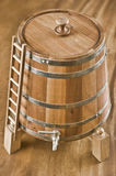 Barrel. Wooden barrel with tap and lid on wooden background Royalty Free Stock Photography