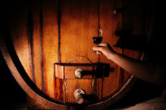 Wine glass in front of wine barrel. Hand holding up a wine glass, half full, in front of an old barrel with tap, dark background Stock Images