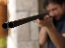 Barrel and aim. Of the double-barreled gun with the blurry face behind Royalty Free Stock Photos