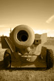 Barrel of artillery field gun. Sepia view looking down barrel of artillery field gun on field with sunset sky in background Royalty Free Stock Image