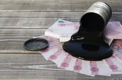 Barrel avec de l'huile, notes chinoises de yuans sur un fond en bois Photographie stock