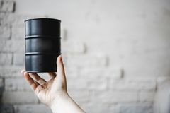 Barrel black with oil in a girls hand against a brick wall. The concept of growth and falling prices in the world market. Stock Photo