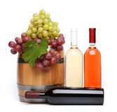 Barrel and bottles of wine and ripe grapes. On barrel on a white background Stock Photos