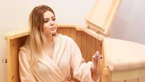Barrel cedar. Wellness spa sauna. Aromatherapy treatment. Young beauty woman. Girl face.  stock photo