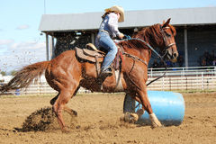 And the barrel falls. Cowgirl running barrels at rodeo Royalty Free Stock Photography