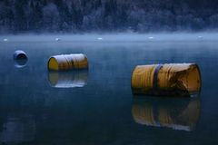 yellow painted old rusty oil barrels float on a lake in winter Stock Photos