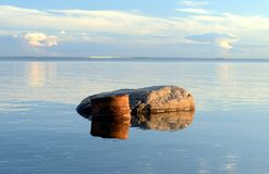 Barrel floating in the water. Next to the stone Royalty Free Stock Images