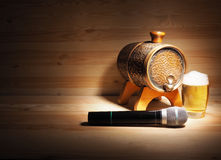 Barrel and glass of beer, microphone on wooden background. concept karaoke Royalty Free Stock Photo