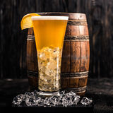 Barrel and glass of light beer with ice and lemon Royalty Free Stock Photo