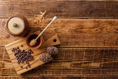 Barrel of honey with pine nuts on a wooden background. Flat lay. Copy space. Barrel of honey with pine nuts on a wooden background. Flat lay. Space under your royalty free stock image