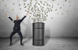 Barrel i carichi con soldi che scoppiano e dall'uomo d'affari felice nella celebrazione della posa Fotografia Stock Libera da Diritti