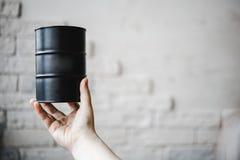 Barrel le noir avec de l'huile dans une main de filles contre un mur de briques Le concept de la croissance et des prix en baisse Photo stock