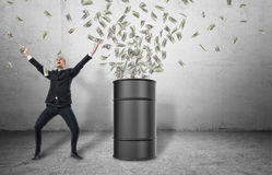 Barrel loads with money bursting out of it and happy businessman in celebrating pose Royalty Free Stock Photo