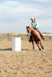 Barrel Racing #2. A barrel racing horse and rider in an outdoor arena. The rider is a female wearing a cowboy hat. The horse is moving quickly around the barrel Royalty Free Stock Photo