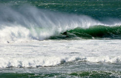 In the barrel. Racing through the barrel of a beautiful offshore wave in Portugal Stock Image