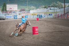 Barrel racing horse and rider swerve around second barrel. Williams Lake, British Columbia/Canada - June 30, 2016: a barrel racer swerves around the second Royalty Free Stock Photo