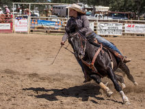 Barrel Racing. A barrel racer riders her horse as she closes in on a barrel. The rodeo in Cottonwood, California is a popular event on Mother's Day weekend in stock image
