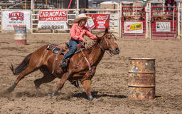 Barrel Racing Rider. A cowgirl rides up to round a barrel during a barrel racing event.   The rodeo in Cottonwood, California is a popular event on Mother's Day Royalty Free Stock Image