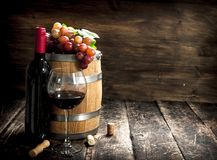 barrel of red wine with grapes and a corkscrew. Stock Photo