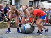 Barrel rolling race. Beer, Devon, UK.14th August 2018: Famous barrel rolling race in main street of Beer during annual Beer Regatta Week event. Four members of Royalty Free Stock Photography