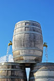 Barrel with two open faucets. Pouring water, blue sky in the background Royalty Free Stock Images