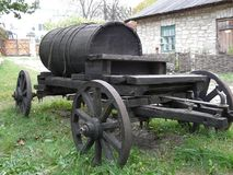A barrel on wheels. An old barrel for water on wheels near the Caucasian house Stock Photography