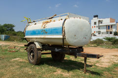 Barrel on wheels. Rusty tank, trailer on wheels, transport liquids, store water, rust, old paint, urban outskirts, Indian landscape, typical india, low-rise Stock Photos