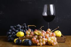 Wineglass with some red wine and ripe grapes of wine on background. Toned. Figs and grapes Horizontal. Barrel, wineglass with some red wine and ripe grapes of Royalty Free Stock Photo