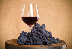 Barrel, wineglass with some red wine and ripe grapes of wine on. Burlap background. Toned royalty free stock images