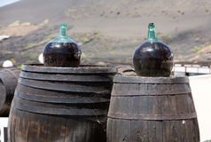 Barrels and  big bottles with grape wine - malvasia.  Lanzarote. Spain Royalty Free Stock Photos