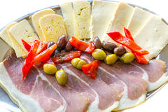 Barrels filled with delicacies cheese ham olives and peppers Stock Photos