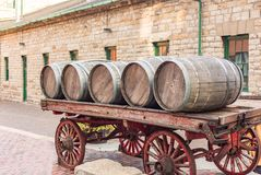 Barrels lined up on a carriage old stone building Royalty Free Stock Images