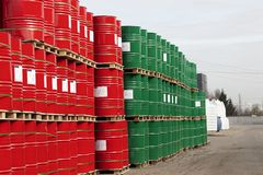 Barrels of 200 liters of metal are in the pallet on the street under the open sky. Red and green barrels for petroleum royalty free stock photo
