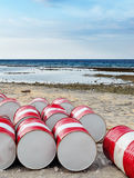 Lot of oil barrels on a seashore. Royalty Free Stock Photos