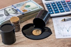 Barrels of oil with dollar banknotes, calculator, profit, business growth graph. On desk Royalty Free Stock Photography